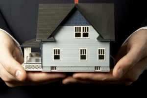 man holding model house